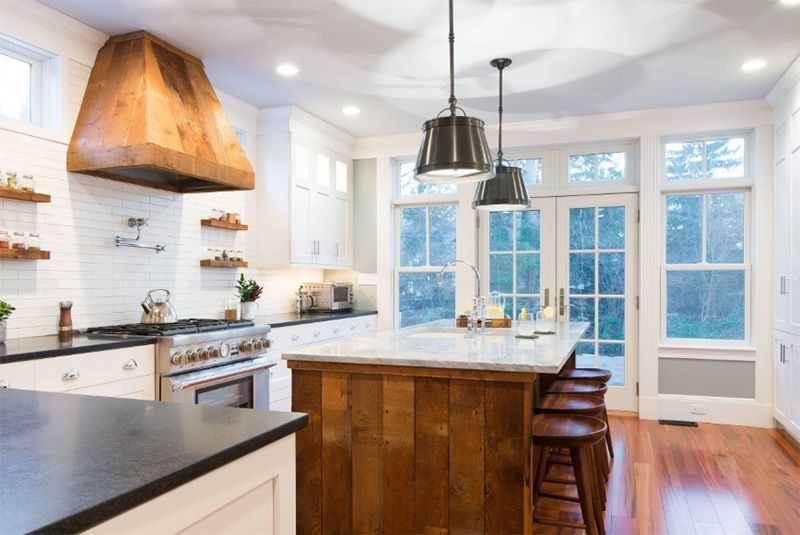 Mẫu nội thất phòng bếp này lấy phông nền là màu trắng sáng để làm nổi bật lên điểm nhấn là bộ bàn ghế, các kệ gỗ và chiếc máy hút khói